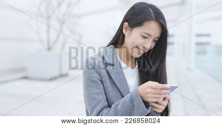 Businesswoman sending sms on cellphone at outdoor