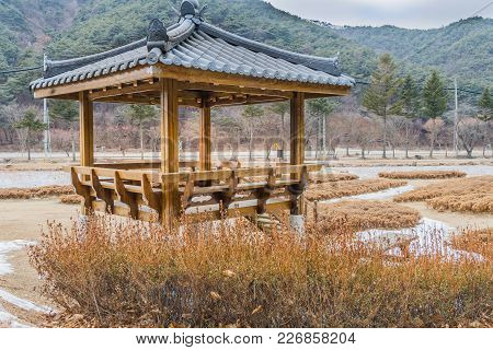 Winter Landscape Of Oriental Gazebo Surrounded By Brown Bushes In A Public Park With Mountains Under
