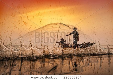 Fishermen Using Nets To Catch Fish At The Bangpra Lake During Sunrise Time.