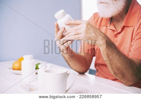 Aged Man Sitting At Table And Reading Instructions On Pill Bottle