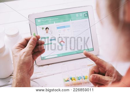 Elderly Patient Having Online Consultation With Doctor On His Tablet Computer