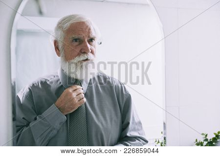 Portrait Of Handsome Senior Man With White Beard Looking At Mirror While Adjusting His Necktie