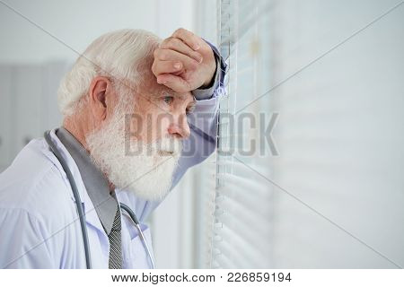 Thoughtful Aged General Practitioner Looking Through Window In His Office