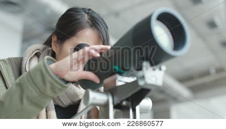 Woman looking through telescope to observe the bird