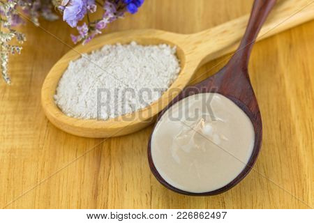 Mixed Australian Clay Powder ready to mask skin, next to dried powdery clay in wooden spoon on wood background, ideally to make home spa beauty product