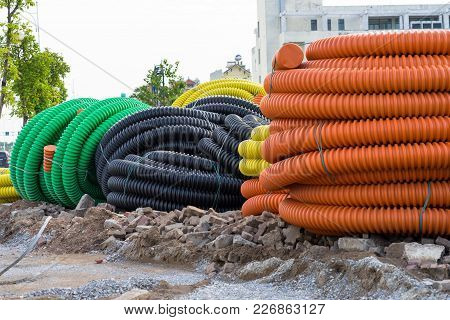 Pile Of Big Industrial Plastic Corrugated Pipes On Ground