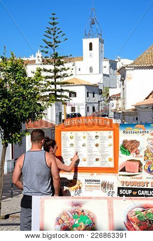 Albufeira, Portugal - June 6, 2017 - A Young Couple Looking At A Menu Board Outside A Restaurant In