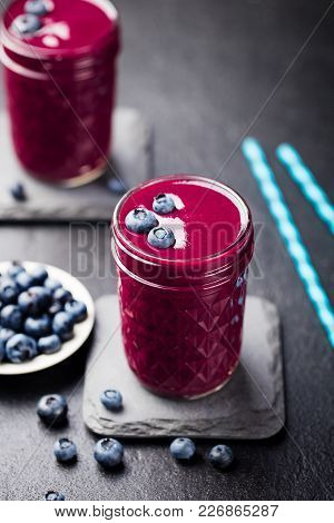 Berry Smoothie With Fresh Blueberries On A Black Stone Background.