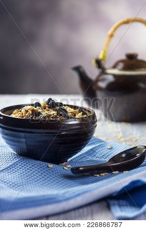 Oatmeal Porridge With Walnuts And Raisins In Bowl - Healthy Rustic Breakfast