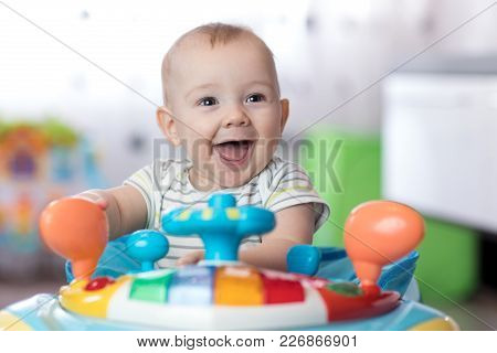 Funny Baby Boy Playing In Baby Jumper