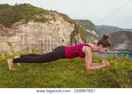 Fitness Woman Doing Elbow Plank Pose On Cliff Near Ocean, Nature Background