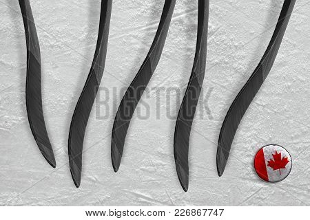 Canadian Puck And Five Sticks On The Ice Of The Hockey Arena. Concept, Hockey