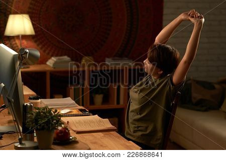 Tired College Student Stretching While Doing Homework In Dark Room In The Light Of Lamp