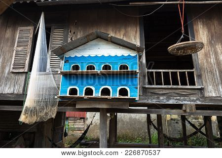 Pigeon Dovecot. Bird Nesting House Hanging In Front Of Old Wooden Champa House In South Of Vietnam