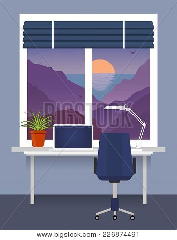 Home Workplace At The Window With Desk, Laptop, Desk Lamp. Room Plant In Pot On The Windowsill. Blin