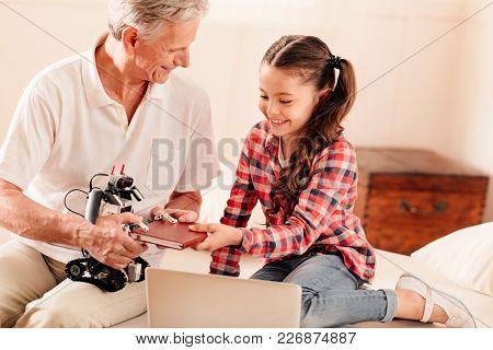 It Is So Strong. Friendly Grandad And His Granddaughter Smiling To Each Other While Both Sitting On
