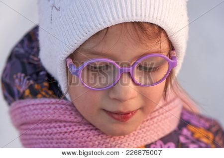 Face Of A Child Girl In Glasses Close-up Illuminated By The Evening Winter Sun. The Girl Is Looking