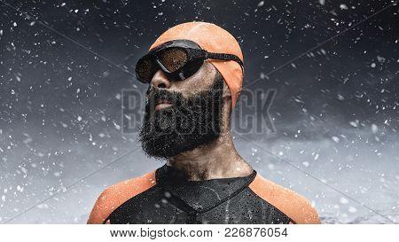 Portrait Of Bearded Scuba Diver Under Rain Drops Over Snow Mountains Background.