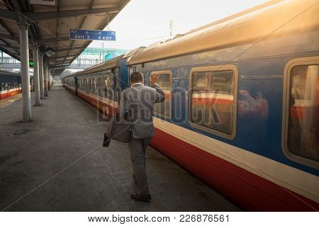 Man Waves Hands Saying Goodbye To People Upon Train Departure