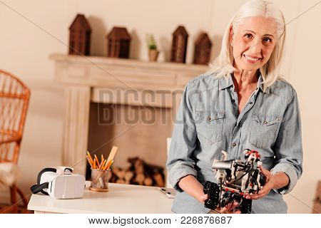 Contemporary Retirement. Waist Up Shot Of Retired Woman Looking Into The Camera With A Cheerful Mile