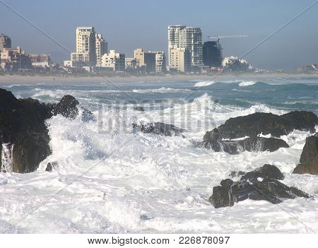 Winter Seascape, With Waves Crashing Over Some Rocks In The Fore Ground And High Rise Buildings In T
