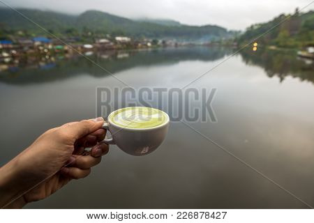 Hot Matcha Latte Green Tea In White Cup On Hand With Water Village At The Edge Of River View, Travel