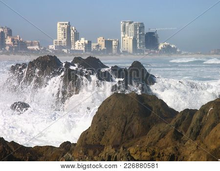 Winter Seascape, With Waves Crashing Over Some Boulders In The Fore Ground And High Rise Buildings I