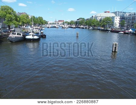 Amsterdam, Netherlands Europe On July 2015: Boats In Canal Gracht Ready To Cruise And Traditional Ho