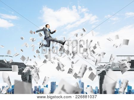 Businessman Jumping Over Gap With Flying Paper Documents In Concrete Bridge As Symbol Of Overcoming
