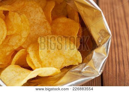 Potato Chips In A Silver Package On A Wooden Background Close Up.