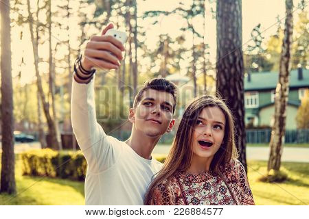 Cute Young Couple Doing Selfie In Summer Park.