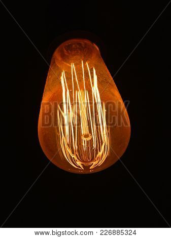 Close Up One Modern Design Electric Light Bulb Over Dark Black Background, Low Angle View