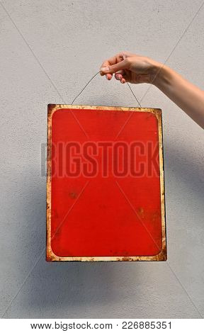 Close Up Woman Hand Holding Red Metal Painted Empty Warning Sign With Copy Space Over Concrete Wall