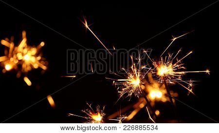 Close Up Group Of Several Festive Firework Sparklers Over Black Background, Low Angle Side View, Sel