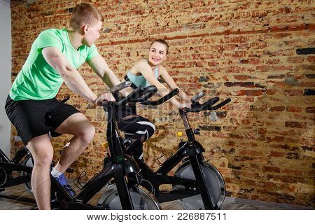 Sporty Woman Using Cycling Exercise Bike With Her Fitness Partne