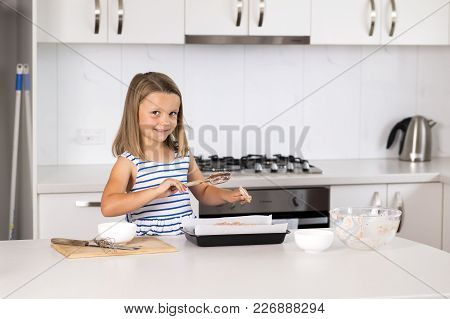 Young Beautiful And Adorable Girl 6 Or 7 Years Old Cooking And Baking At Home Kitchen Preparing Choc