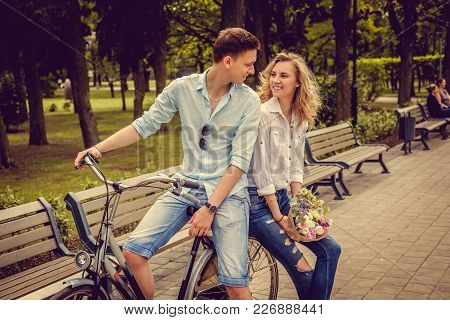 Joyfull Couple Posing On One Bicycle In A City Summer Park.