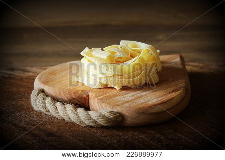 Nest Of Pasta Tagliatelle On Wooden Cutting Board Aon Rustic Background. Selective Focus .