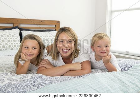 Young Blond Caucasian Woman Lying On Bed Together With Her Little Sweet 3 And 7 Years Old Son And Da