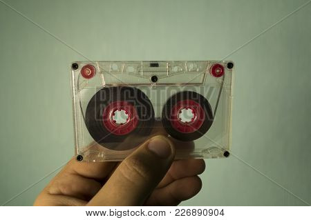 Transparent Audio Cassette In Hand On A Blue Background