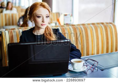 Portrait Of A Young Beautiful Businesswomen Enjoying Coffee During Work On Portable Laptop Computer,