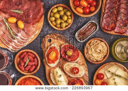 Typical Spanish Tapas Concept. Concept Include Slices Jamon, Chorizo, Sausage, Bowls With Olives, To