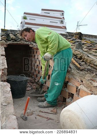 Alora, Spain - December 1, 2011: Man Demolishing Roof Tiles At Village House In Andalusia To Create
