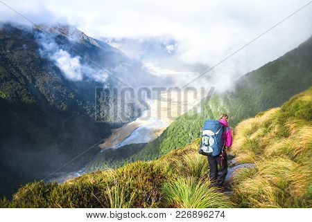 A Hiker Walks Along A Trail In The Matukituki Valley In Mt. Aspiring National Park, New Zealand.