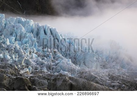 Dense Fog Rolls In Over The Fox Glacier On The South Island Of New Zealand.