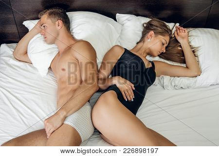 Upset Young Couple Lying Separate In A Bed After Family Conflict.