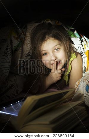 Little Caucasian 6-8 Years Old Girl Reading A Book Under Bed Cover In The Bed Night Under Bed Cover