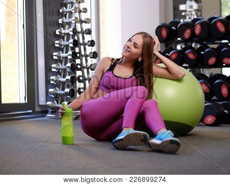 Smiling Sporty Female Sits On The Floor Near The Green Pilates Fitness Ball In A Gym Club.