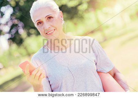 Pleasant Mood. Close Up Of Smiling Elderly Woman Keeping Mobile Phone In Hand While Listening To Mus