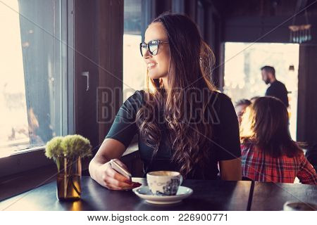 Smiling Brunette Woman Using A Smartphone In A Cafe.